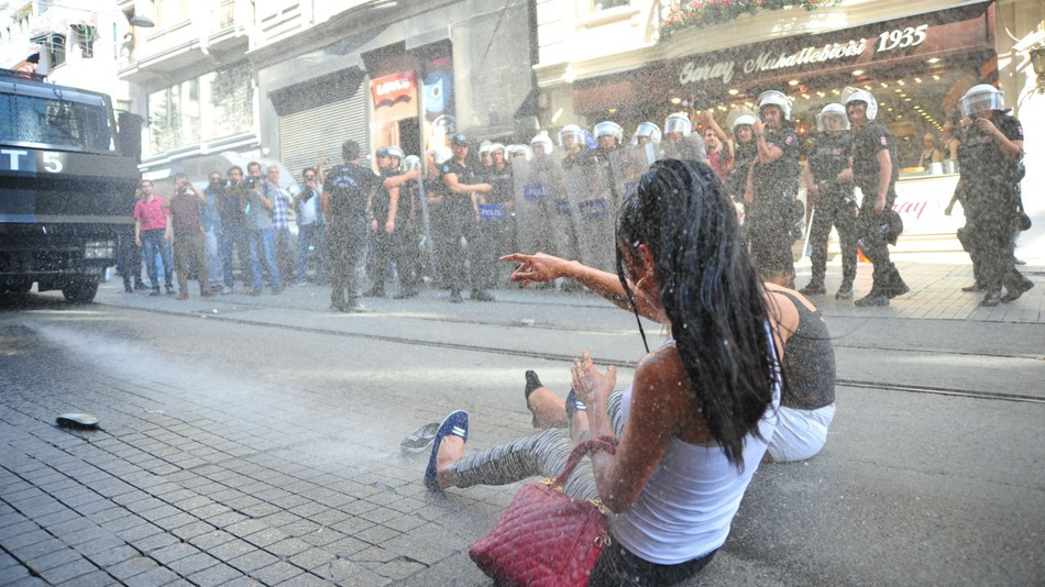 A participant at Istanbul resists the use of water canon by Police(Photo: Reuters)